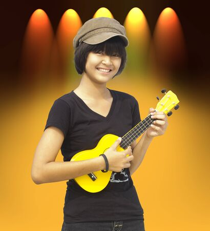 Little girl playing guitar, look to the camera and smile photo