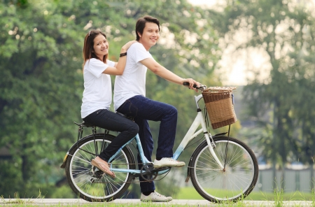 Young couple. Cycling in the park photo