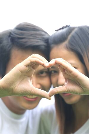 Young couple show love shape hand photo