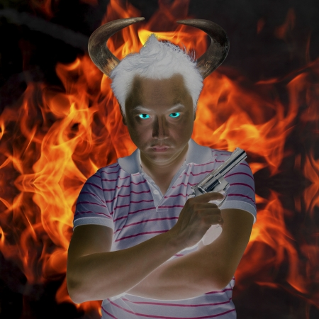 Devil holding gun with fire background Stock Photo - 17381286