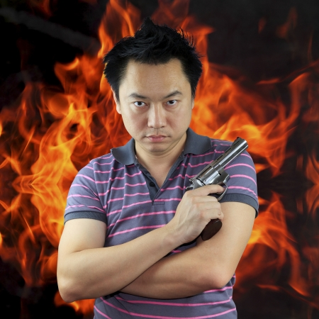 Man holding gun with fire background Stock Photo - 17381282