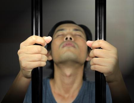 Man Hands of the prisoner on a steel lattice Stock Photo - 17501263