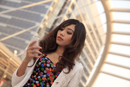 Asian working woman holding smart phone in the city photo