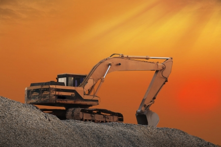Excavator machine on the orange sky at evening photo