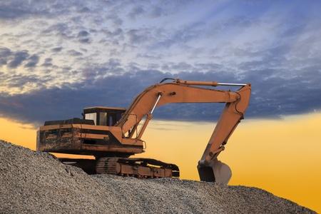 Excavator machine on a blue orange sky photo