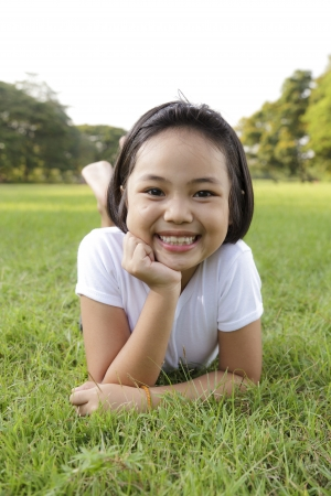 Asian little girl relax and smiling happily in the park photo