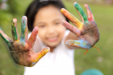 Asian little girl with hands painted in colorful paints photo