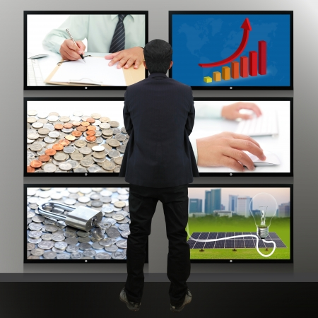 Businessman standing looking at the TV screen photo