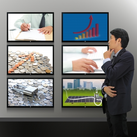 lcd screen: Businessman standing looking at the TV screen