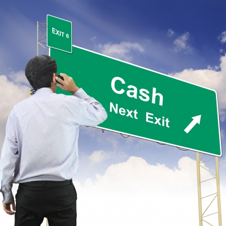 galvanised: Businessman talking the phone standing in front Road sign concept with the text Cash Stock Photo