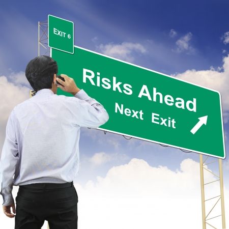 risks ahead: Businessman talking the phone standing in front Road sign concept with the text Risks Ahead Stock Photo