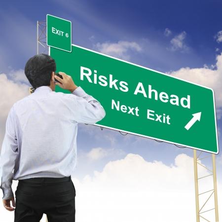 risks ahead: Hombre de negocios hablando al tel�fono de pie en el concepto de signo de carretera frente con el texto Riesgos Ahead Foto de archivo