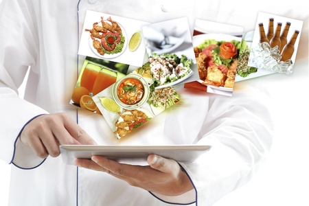 Chef using digital tablet with images of variety food