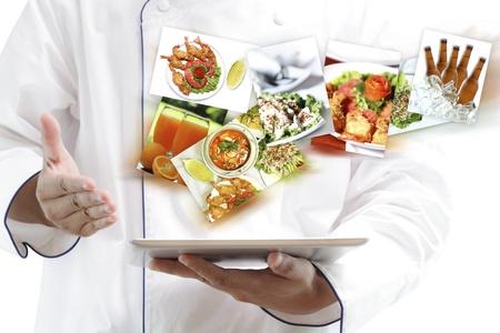 negocios comida: Chef que usa la tableta digital con im�genes de comida variedad