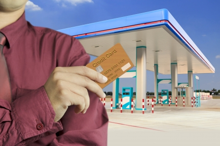 credit card debt: Cropped view of Businessman hand holding credit card in gas station Stock Photo