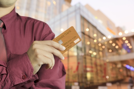 Cropped view of Businessman hand holding credit card in department store photo