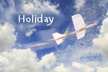 Airplane model on blue sky and Holiday text