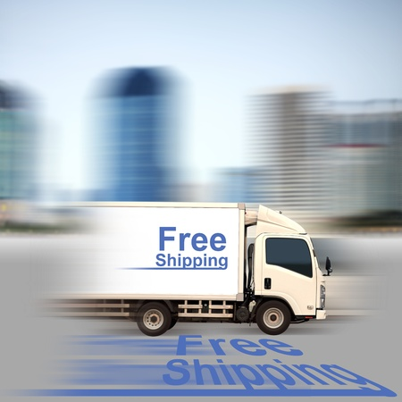 White van with Free Shipping and office buildings in the city photo