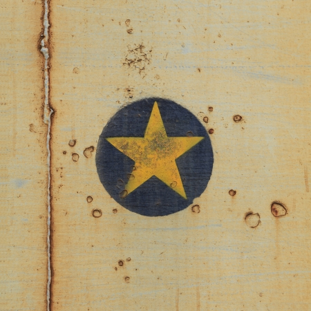 Yellow star on old steel background photo