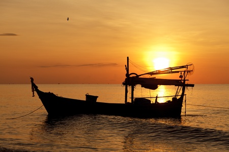 Silhouette of fishing boat at sunset photo