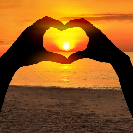 Two hands of lovers on the background of sunset on the sea  photo