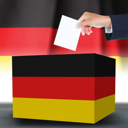 Hand holding ballot and box with the Germany flag in the background photo