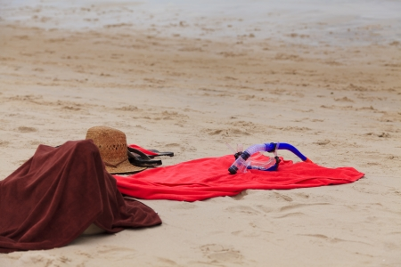 Hat, slippers and snorkel on the beach photo