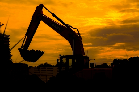 Silhouetted Excavator Stock Photo