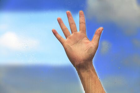 Hand on the glass with blue sky photo