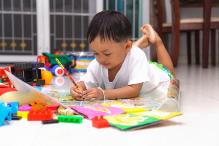 babies with toys: Happy little boy drawing and reading lying on the floor at home