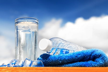 Glass of water and bottle with blue sky photo