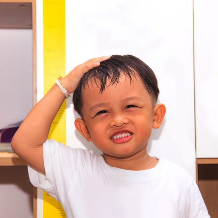 tallness: Little boy measuring his height  Stock Photo