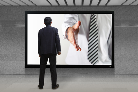 Business man gives a handshake out of TV screen photo