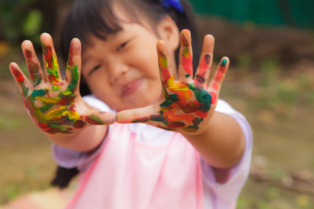 Little girl with hands painted in colorful paint  photo
