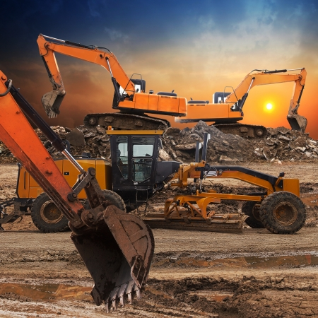 Excavator and grader working at construction site