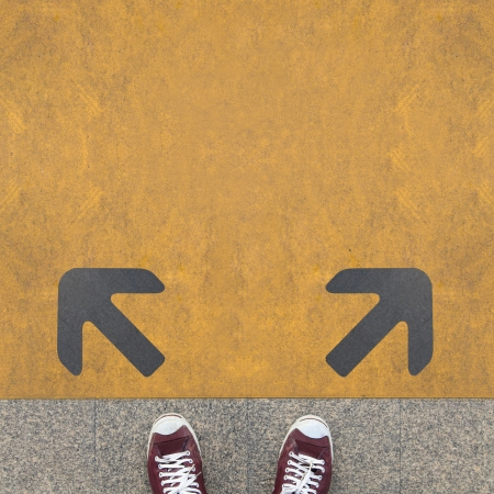 confused: Pair of shoes standing on a road with two grey arrow on the yellow  Stock Photo