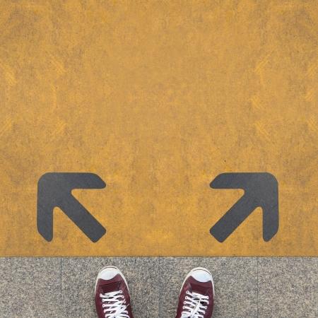 persona confundida: Par de zapatos de pie en un camino con dos flecha gris en el amarillo