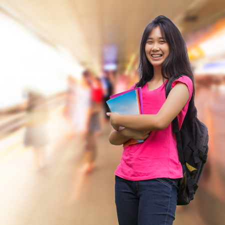 Asian schoolgirl with people walking in skytrain station photo