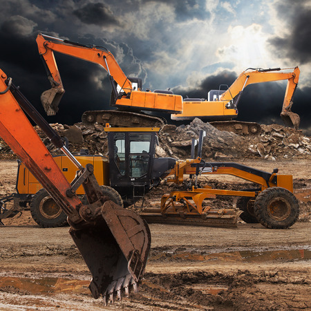 earth moving equipment: Excavator and grader working at construction site