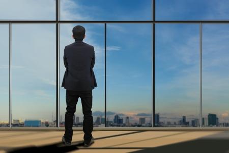 Businessman looking through window  Stock Photo