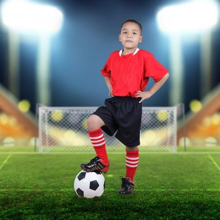 divertirsi: Bambino giocatore di calcio sul campo di calcio con faretti luminosi