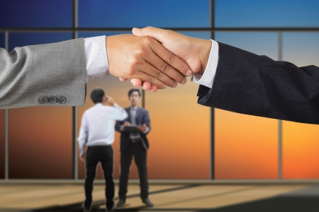 Business people handshaking on background of modern office photo