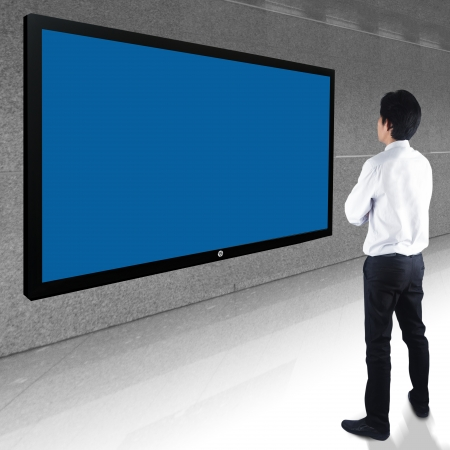 Businessman standing looking at blank TV screen  Stock Photo