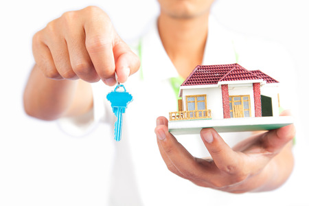 Man holding house key and house model photo