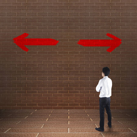 Businessman looking at arrows on the wall