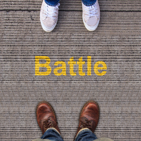 Two pairs of shoes standing on walkway with Battle photo