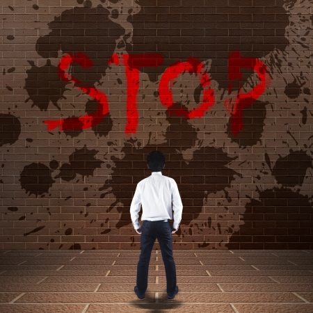 Businessman looking at stop on the wall photo