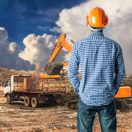 heavy equipment: Construction worker at construction site in blue sky