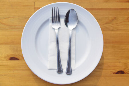 Fork and spoon and plate on table photo
