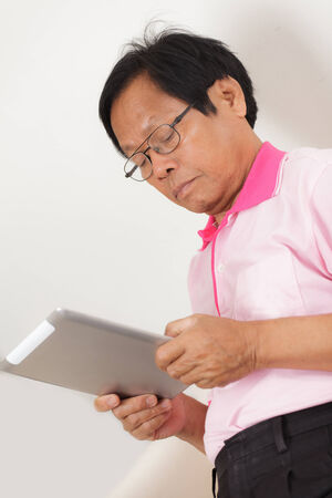 Senior man using digital tablet at home photo
